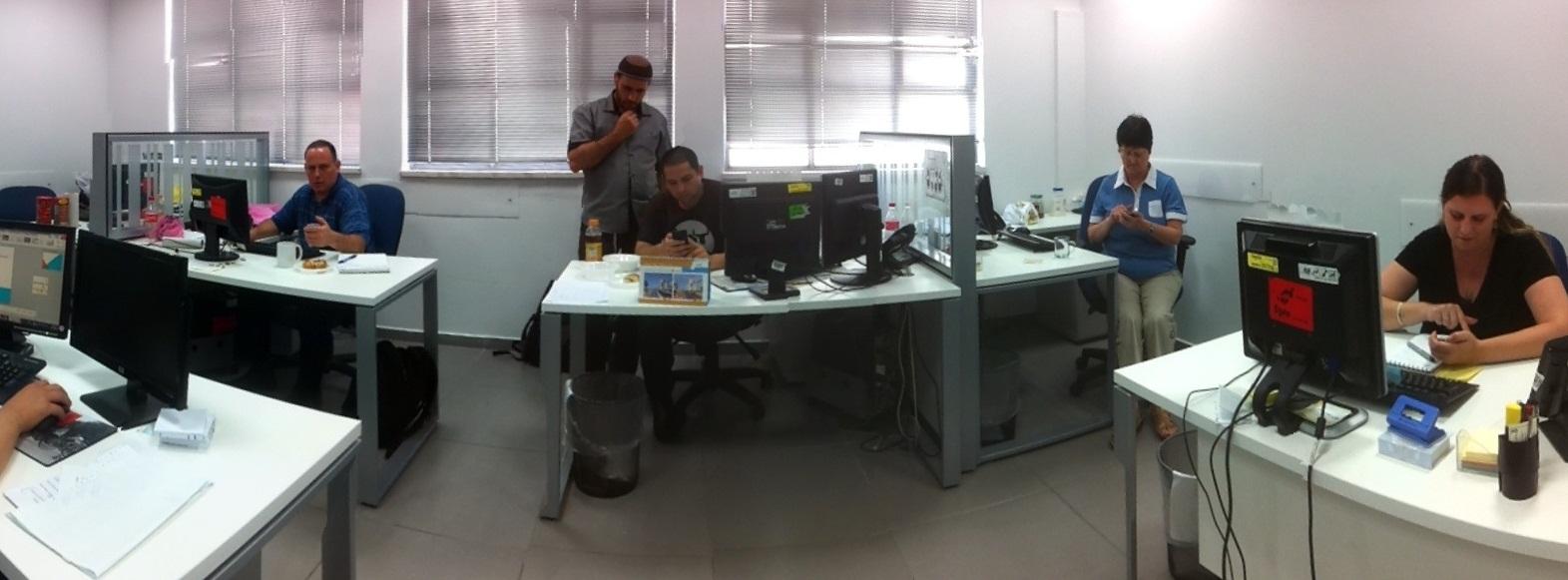 שם השולח: יעל חקשוריאן. תמונה של יום עבודה שגרתי של הצוות שעובד איתי במשרד.  גם לאלו שיש יותר ממסך מחשב אחד על השולחן, עדיין כולם עסוקים גם עם המסך של הסמארטפון. צלמתי את התמונה באמצאות האייפון שלי, עם אפליקציה שמאפשרת לצלם תמונה פנורמית - Photosynth.