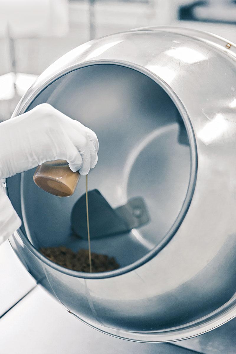טכנאי מוזג משפר טעם, אשר יכול לכלול חלבונים, שמרים ונוגדי חמצון על מזון כלבים חסר טעם במכשיר ציפוי ידני, אשר מסתובב כדי לצפות את החלקים באופן שווה.