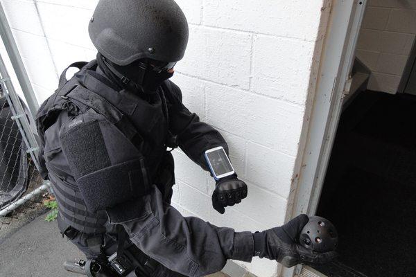 בתמונה: קצין משטרה מתכונן לזרוק את המצלמה לחדר מדרגות סמוי. מקור: Bounce Imaging