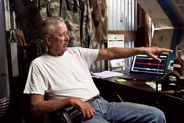 מארק כריסמון מנטר פעילות סיסמית שנגרמת על ידי בארות הזרקה, בביתו שבאוקלהומה, כחלק מרשת סיסמית שהותקנה על ידי מדענים (תמונה: מדע פופולארי)