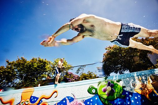 Man diving into outdoor swimming pool, Getty Images Israel, Jonathan Knowles