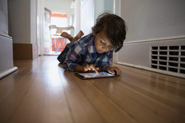 Boy using digital tablet on hallway floor