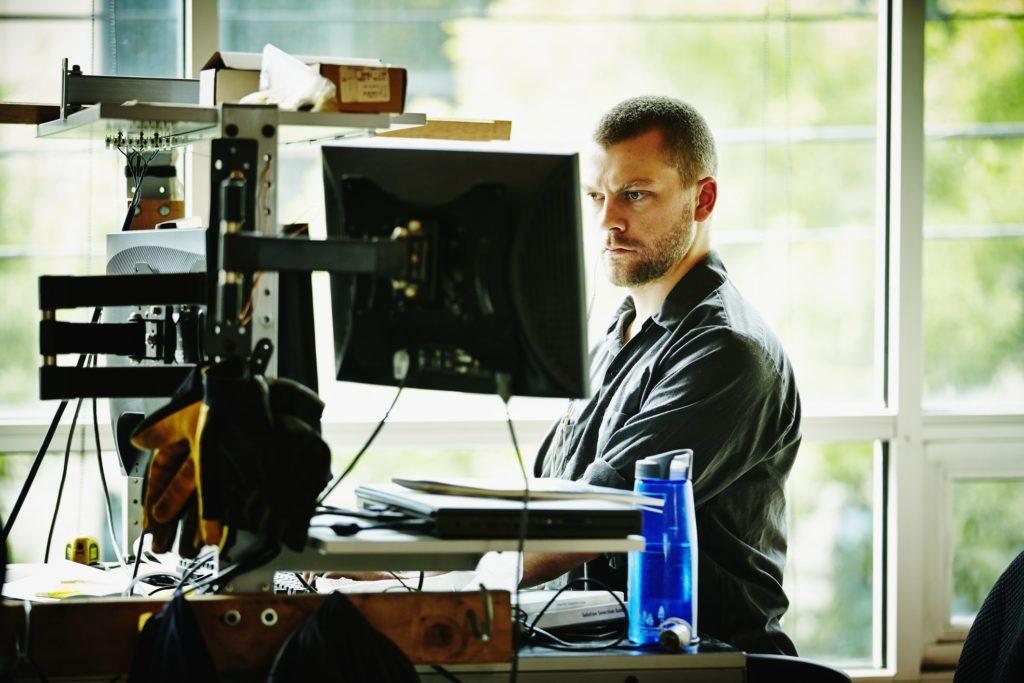 Engineer standing at desk in workshop designing project on computer