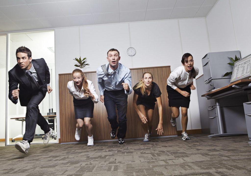 Businessmen and businesswomen racing in office