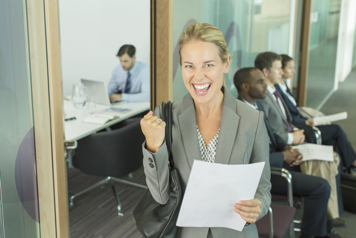 Businesswoman cheering in office getty images