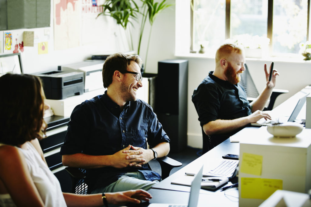 Laughing coworkers sitting at workstations in startup office discussing project