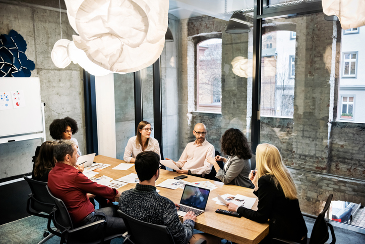 A group of young people, male and female, of different ethnicities are sitting in a bright modern office room. They are discussing something during a business meeting. There are documents and laptops on the table.