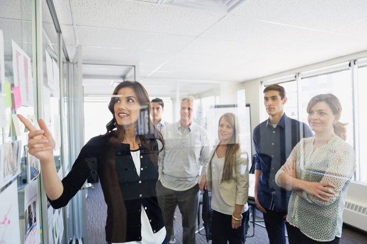 Businesswoman discussing project with colleagues in office